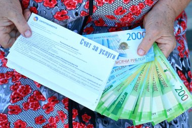 The bill for the service and the new Russian banknotes in the hands of an elderly woma
