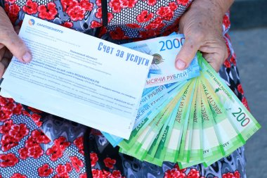 Receipt for electricity and Russian money in the hands of an elderly woma