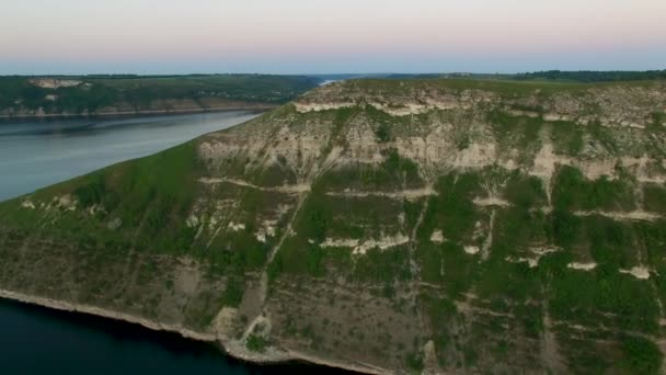 Majestic aerial drone flight through Ukrainian landscape river Dnister. Steep shore with stones. Nature without people. Sunset. 4K
