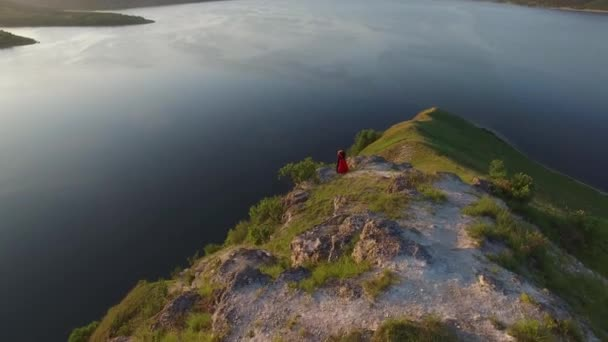 Aerial flight above couple in love standing in cliff edge near water. Woman in amazing red dress. Man in black. Sunset.