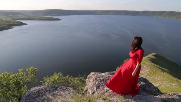 Beautiful dark hair woman in red dress posing for the camera on huge river bank edge.