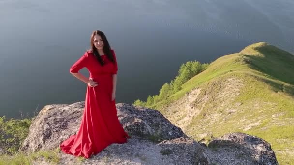 Beautiful european woman in red dress turns to camera on large river bank edge. Amazing background. Huge river. Sunset.