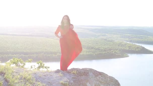 Beautiful european woman playing with her red dress on large river bank edge. Amazing background. Huge river. Sunset.