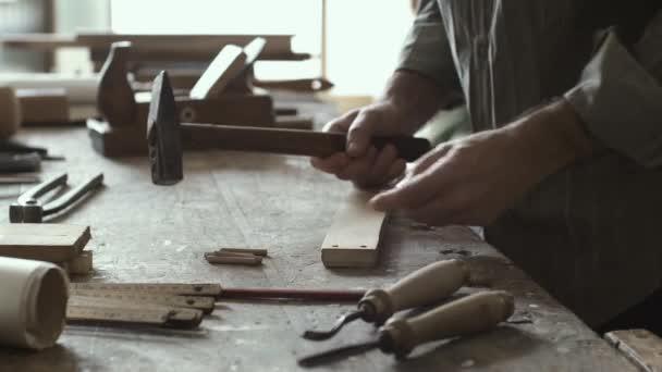 Zkušený tesař zatloukání kolíků k dřevěné spoje, koncept tesařské a zpracování dřeva