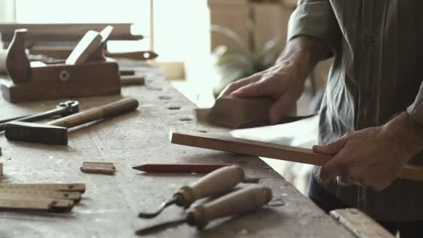 Tesař, pracoval v jeho dílně, on je vyhlazení dřevěný povrch brusným papírem