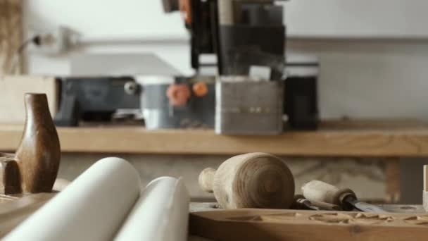 professioneller Tischler, der in der Werkstatt arbeitet und Holz mit einem Hohlmeißel schnitzt