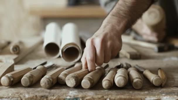 Profesionální kvalifikací tesaře řezbářské dřevo pomocí kladivo a dláto a sady dřevoobráběcích nástrojů v popředí