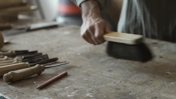 Tesař, čištění workbench se štětcem a Dřevoobráběcí nástroje, zručnost a tesařství koncept