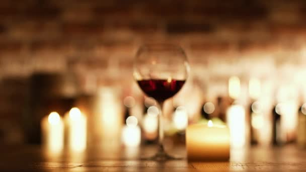 Sommelier drinking a glass of red wine in the cellar, collection of bottles and lit candles: wine culture and winemaking concept