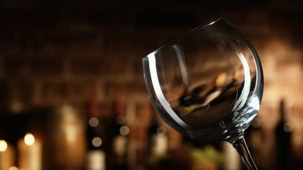 Sommelier degustaci vína ve sklepě, nalévá vynikající červené víno ve skle.
