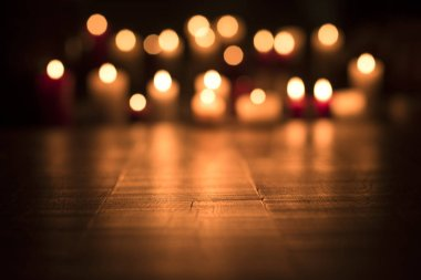 Defocused lit candles burning in the Church, spirituality and religion concept