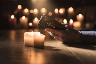 Religious man reading the Holy Bible and praying in the Church with lit candles, religion and faith concept