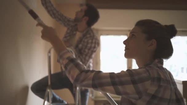 glückliches Paar renoviert sein neues Haus und streicht gemeinsam Innenwände: Lifestyle, Home Makeover und Umbaukonzept