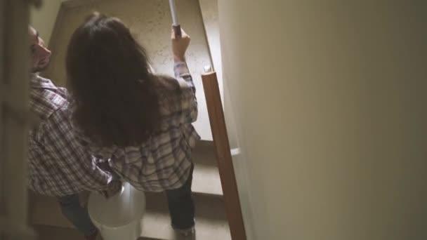 Mladým manželům pohybující se v jejich novém domě, jsou malby stěn, dělá domácí člověka a kreslení na projektu: real estate, domácí koncept renovace a životního stylu, videomontáž