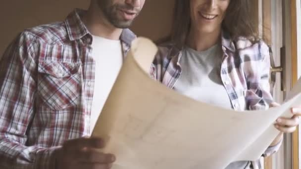 Young happy couple moving in their new house, they are painting walls and doing a home makeover: real estate and home renovation concept, video montage