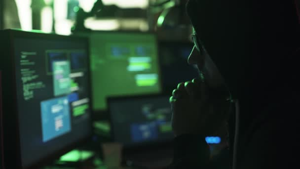 Nerd hacker with hoodie working at desk late at night, he is watching multiple screens and hacking networks, cyber security concept
