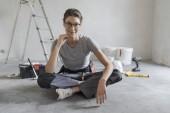 Atraktivní usmívající se žena renovovat svůj dům, ona sedí na podlaze s nástroji a lodě, domácí pojetí člověka