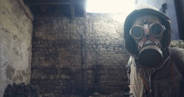 Nuclear disaster survivor in a post apocalyptic setting, he is wearing a gas mask and walking in a destroyed city