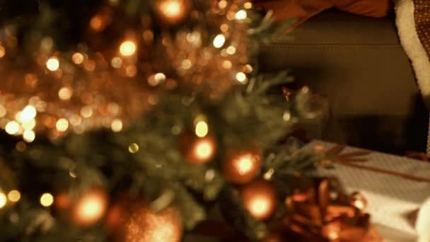 Netter Junge, der zu Hause auf dem Sofa neben dem Weihnachtsbaum schläft, wartet an Heiligabend auf den Weihnachtsmann: Kindheits- und Urlaubskonzept