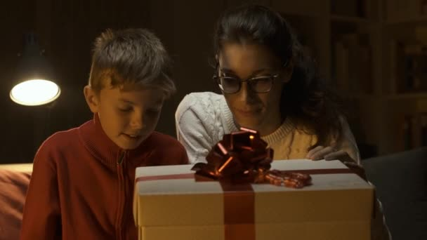 Happy boy and his mother opening a beautiful Christmas gift with a magical surprise: holidays and togetherness concepts