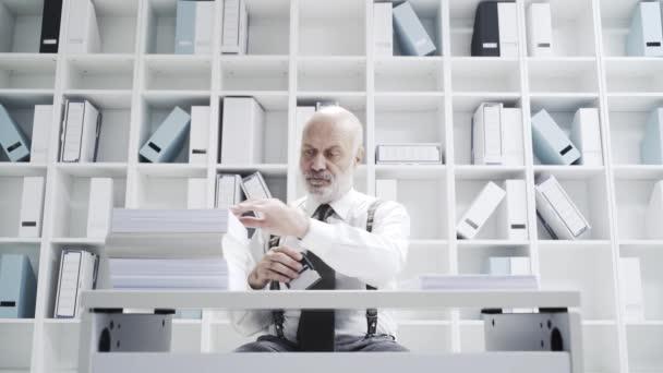 Büroarbeiter macht langweilige, sich wiederholende Arbeit in seinem Büro: Er stempelt einen Stapel Papierkram ab