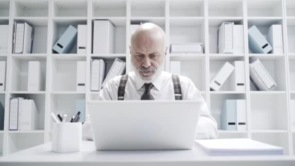 Angry stressed mature businessman breaking his laptop, he is having problems with his computer