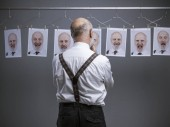 Mature businessman staring at his multiple personalities and expressions on a collection of hanging portraits: mind self analysis and emotions concept