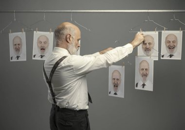 Mature businessman staring at his different personalities on a collection of hanging portraits and making a comparison: mind self analysis and emotions concept