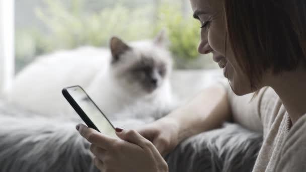 Šťastná mladá žena připojení a chatování s její smartphone doma, její kočka leží vedle ní přední okno
