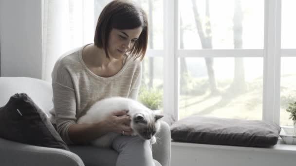 glücklich junge Frau sitzt auf dem Sessel zu Hause, sie hält und streichelt ihre schöne Katze, Haustiere und Lifestyle-Konzept
