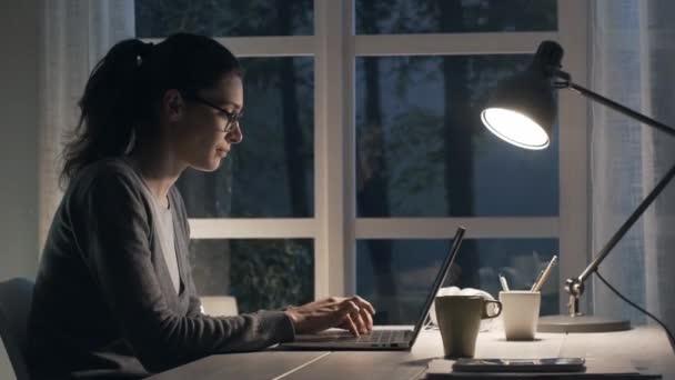 Fáradt nő ül íróasztal otthon és a munka vele laptop, késő este, ő az álmos és birtoklás és a fejfájás, a stressz és a határidők