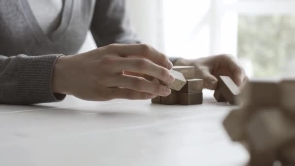 Woman playing with a wooden brain teaser puzzle, she is trying to put pieces together, problem solving concept