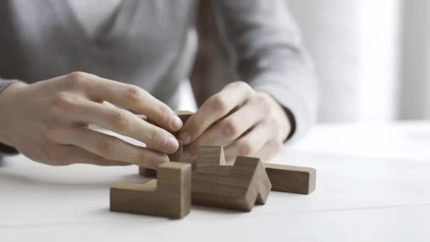 Smart woman playing with a wooden brain teaser puzzle on a desk, she finds a solution and solves it