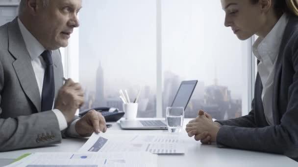 Unternehmensberater, die einen Kunden finanziell beraten, prüfen Berichte und besprechen Lösungen gemeinsam im Büro