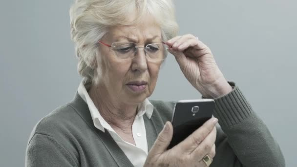 Starší žena s problémy se zrakem pomocí chytrého telefonu