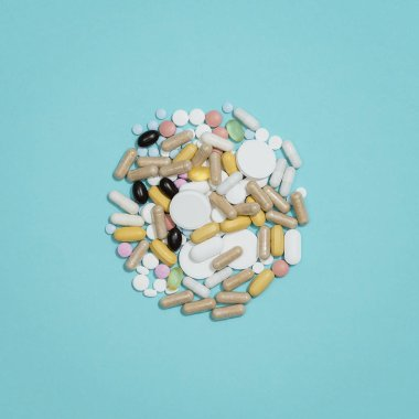 A lot of assorted pills and medicines on blue background