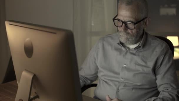 Müder Senior arbeitet nachts am Computer