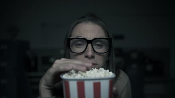 Egy nő horror filmeket néz otthon.