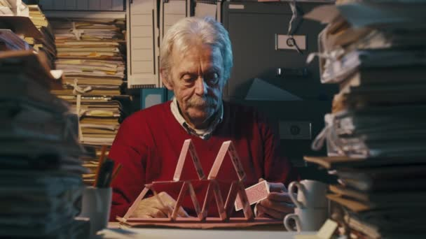 faule Bürokauffrau baut eine Kartenburg auf dem Schreibtisch