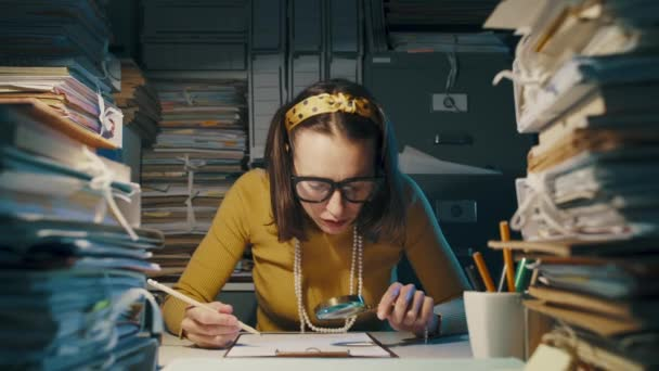 Businesswoman checking a document with a magnifier