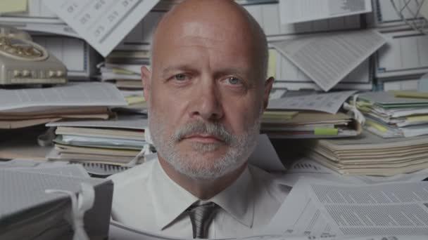 Stressed businessman overloaded with paperwork