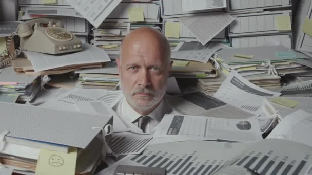 Stressed angry businessman overloaded with paperwork