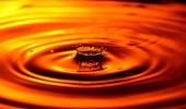 Chiuda sulla vista di goccia che cade in liquido arancione