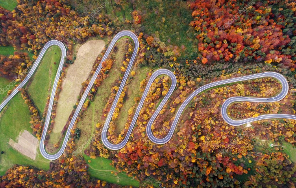 Aerial view of curvy road among autimnal scenery