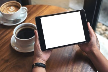Mockup image of hands holding black tablet pc with white blank screen and coffee cups on table