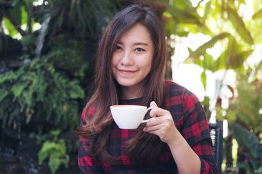 Closeup portrait image of a beautiful Asian woman holding a white mug and drinking hot coffee with feeling happy in green nature and waterfall garden background