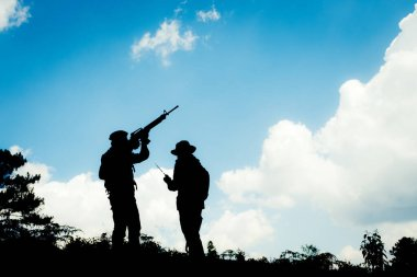 Silhouette image of two armed soldiers with blue sky background
