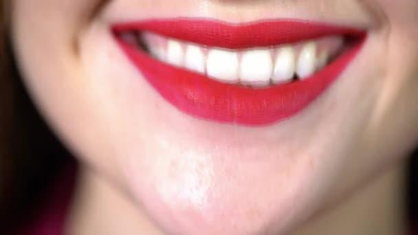 Verführerisches strahlenden Lächeln der Mädchen Nahaufnahme, roten Lippenstift auf den Lippen, Schneewittchen sogar Zähne mit rotem Lippenstift, eine Frau lächelt, verschmiert beißt spielerisch ihre Lippen