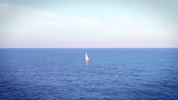 Loď plachetnice s bílými plachtami na otevřeném Středozemním moři. Čas západu slunce denní