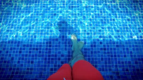 Pánské bosých nohou relaxační v zářivě modré bazénu, podvodní shhot. Voda s sluneční odraz, dovolená, klid, útočiště koncepce